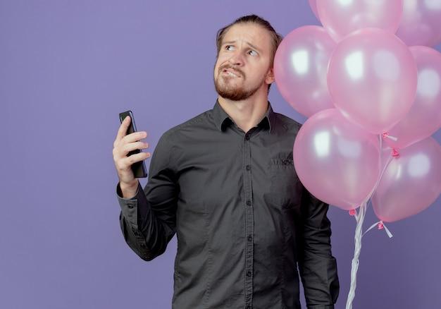 Hombre guapo confundido se encuentra con globos de helio sosteniendo el teléfono mirando hacia arriba aislado en la pared púrpura