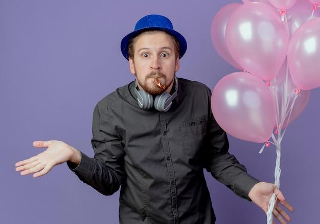 Hombre guapo confundido con sombrero azul y auriculares en el cuello se encuentra con globos de helio que soplan silbato aislado en la pared púrpura