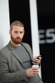 Hombre guapo confundido con teléfono