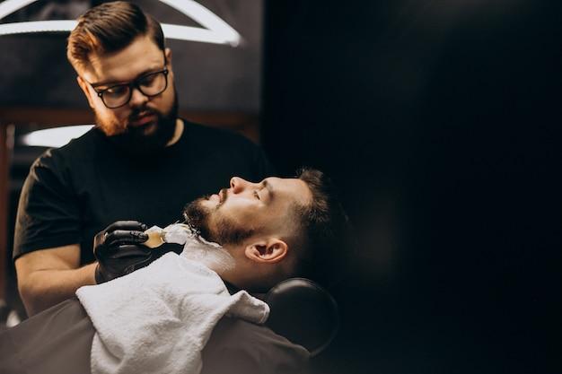 Hombre guapo cortando barba en un salón de peluquería