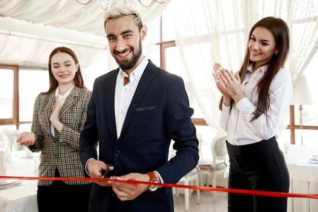 Hombre guapo está cortando la cinta roja en la gran inauguración de un restaurante con dos hermosas asistentes mujeres