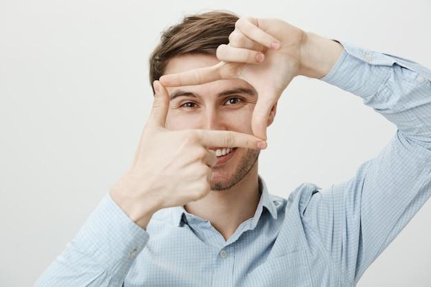 Hombre guapo creativo mostrando marcos de mano, momento de captura