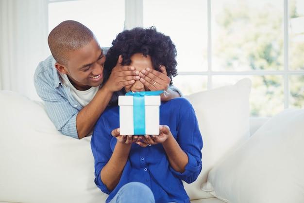 Hombre guapo cubriendo los ojos de su novia en el sofá