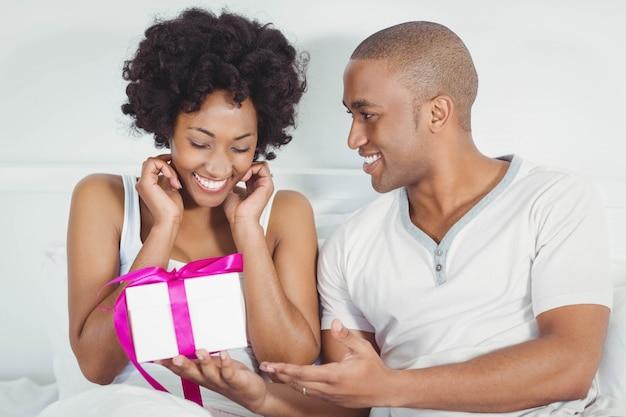 Hombre guapo dando presente a su novia en la cama