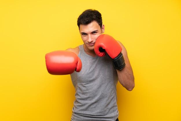 Hombre guapo deporte sobre pared aislada con guantes de boxeo