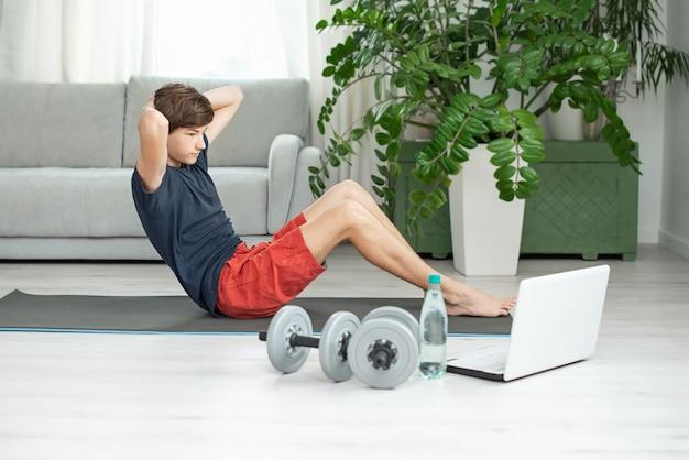 Hombre guapo va deportes en casa en línea. adolescente está entrenando solo en la habitación