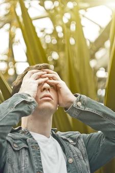 Hombre guapo en la depresión. hipster no afeitado en un jardín botánico, aferrado a su cabeza. concepto: dolor de cabeza y dolor.