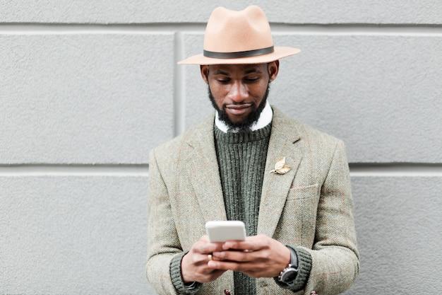 Hombre guapo desplazándose en las redes sociales en su teléfono