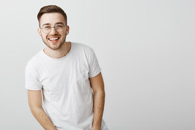 Hombre guapo con dientes blancos, sonriendo y con gafas sobre pared gris