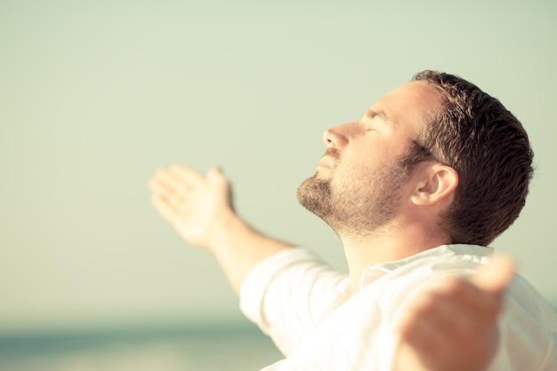 Hombre guapo disfrutando de la vida en la playa concepto de libertad y vacaciones de verano