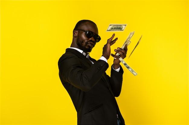 Hombre guapo dispersa dinero y se ve egoísta