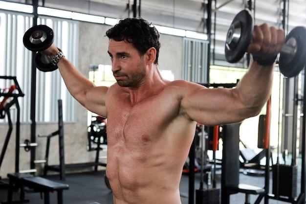 Hombre guapo ejercicio en gimnasio culturismo con cuerpo musculoso fuerte