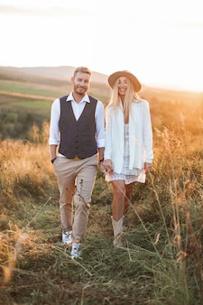 Hombre guapo elegante en camisa, chaleco y pantalón y bonita mujer boho en vestido, chaqueta y sombrero caminando en el campo