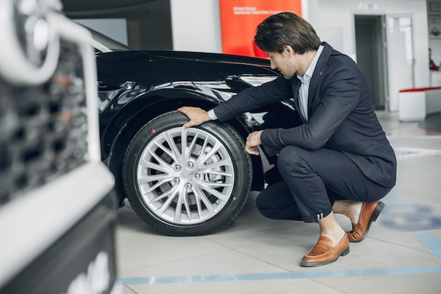 Hombre guapo y elegante en un salón del automóvil