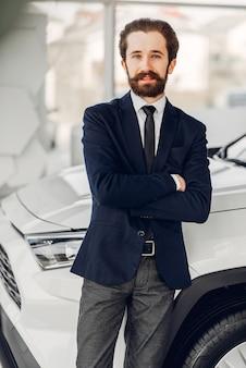Hombre guapo y elegante en un salón de autos.