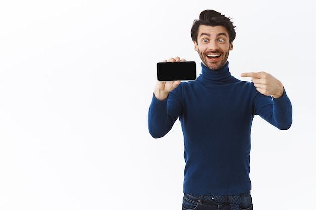 Hombre guapo con elegante suéter de cuello alto, sosteniendo el teléfono inteligente horizontalmente, señalando la pantalla del móvil y sonriendo asombrado, encontró una excelente aplicación y recomienda descargar, pared blanca