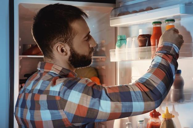 Hombre guapo eligiendo bebida en el refrigerador por la noche