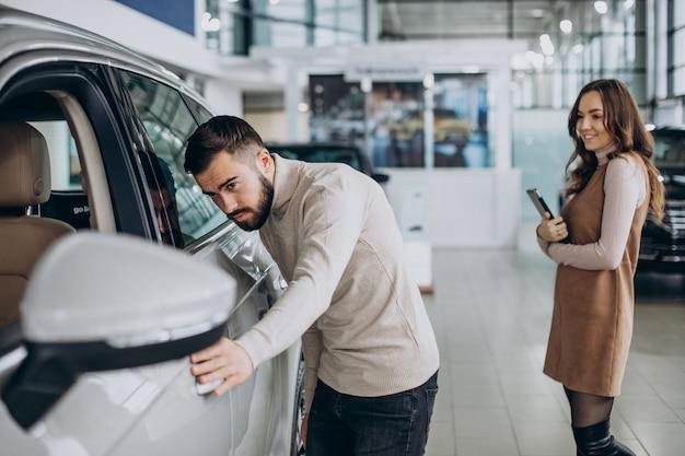 Hombre guapo eligiendo un coche en una sala de exposición de coches