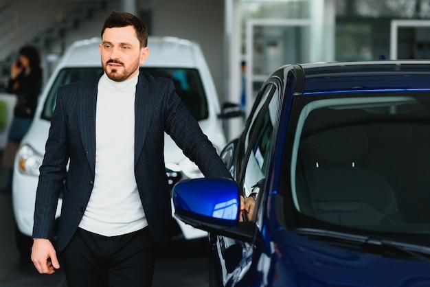 Hombre guapo eligiendo un coche en una sala de exposiciones