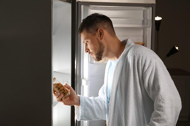 Hombre guapo eligiendo comida en el refrigerador por la noche