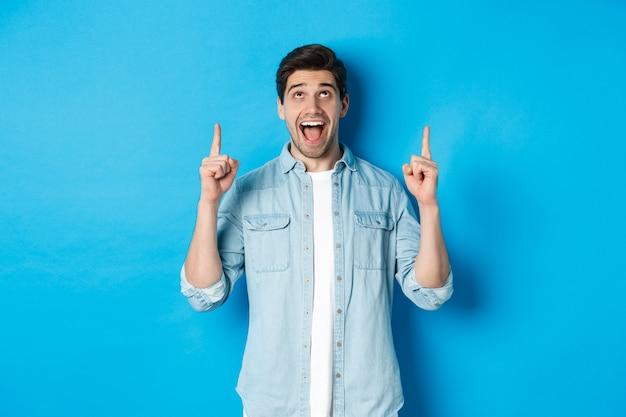 Hombre guapo emocionado apuntando y mirando hacia arriba, mostrando publicidad, de pie sobre fondo azul