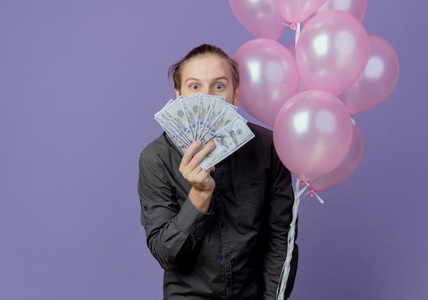 Hombre guapo emocionado se encuentra con globos de helio sosteniendo y mirando por encima del dinero aislado en la pared púrpura