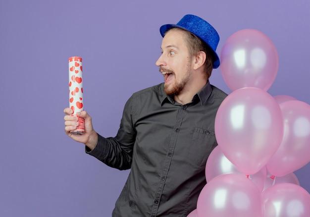 Hombre guapo emocionado con sombrero azul se encuentra con globos de helio sosteniendo y mirando el cañón de confeti aislado en la pared púrpura