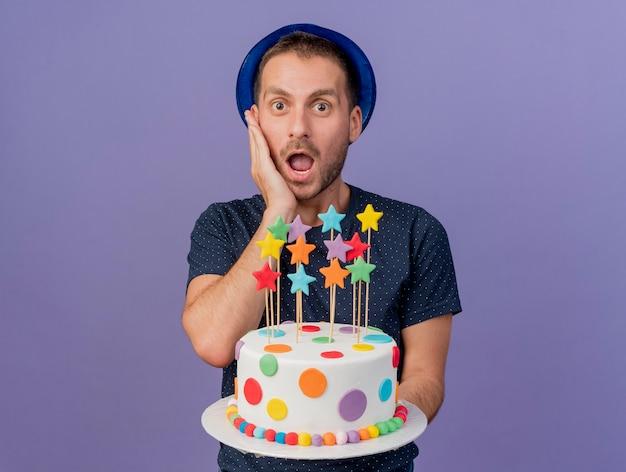 Hombre guapo emocionado con sombrero azul pone la mano en la cara y sostiene la torta de cumpleaños aislada en la pared púrpura