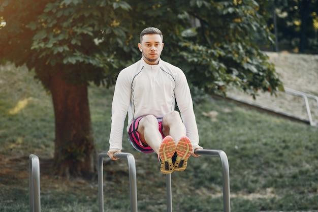 Hombre guapo entrenando en un parque de verano