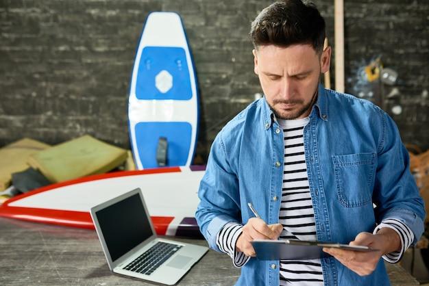 Hombre guapo escribiendo en portapapeles en tienda de tablas de surf personalizadas