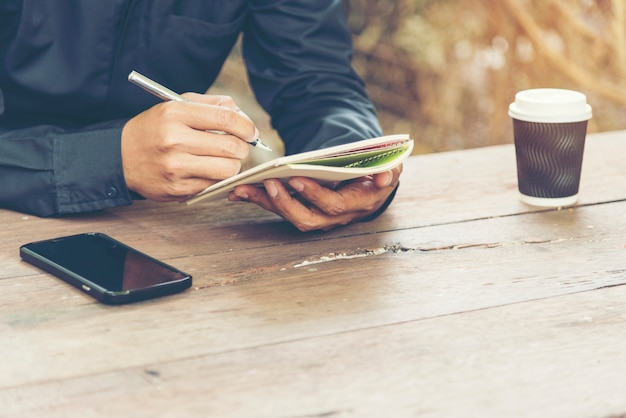 Hombre guapo escribir diario de nota sobre la mesa de madera con teléfono móvil y taza de café.