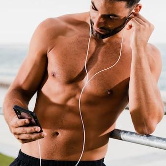 Hombre guapo escucha música al aire libre mientras entrena