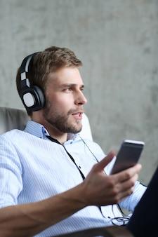 Hombre guapo escuchando música con auriculares