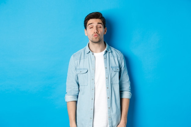 Hombre guapo esperando un beso, fruncir los labios y cerrar los ojos mientras está de pie contra el fondo azul