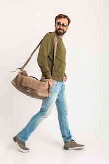 Hombre guapo con estilo barbudo caminando aislado vestido con sudadera con bolsa de viaje, jeans y gafas de sol