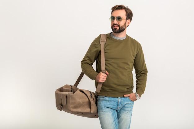 Hombre guapo con estilo barbudo posando aislado vestido con sudadera con bolsa de viaje, jeans y gafas de sol