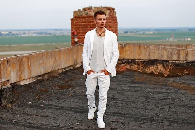 Hombre guapo con estilo en una camiseta blanca, jeans y zapatos caminando en el techo.