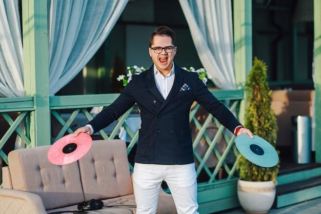 Hombre guapo con estilo con discos de vinilo en manos posando afuera cerca del café al aire libre