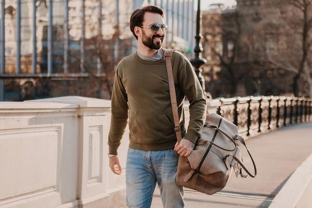 Hombre guapo con estilo hipster caminando en la calle de la ciudad con bolso de cuero con sudadera y gafas de sol, tendencia de estilo urbano, día soleado, viajero feliz sonriente