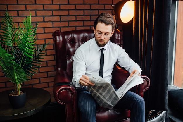 Hombre guapo con estilo millonario en traje azul en casa sentado en el sofá y leyendo el periódico.