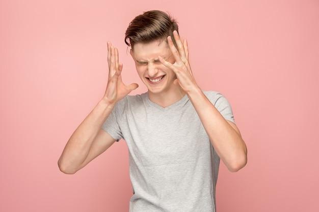 Hombre guapo en estrés aislado en rosa