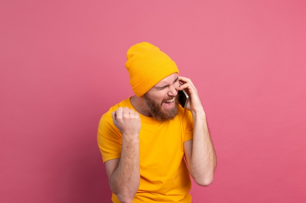 Hombre guapo europeo hablando por teléfono inteligente gritando orgulloso y celebrando la victoria y el éxito muy emocionado en rosa