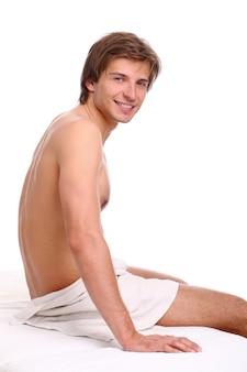 Hombre guapo y feliz en camilla de masaje