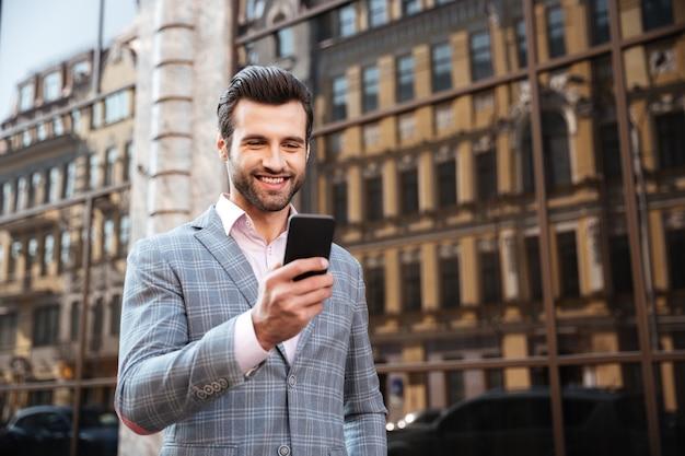 Hombre guapo feliz en chaqueta mirando teléfono móvil