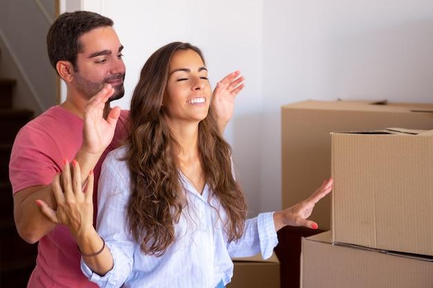 Hombre guapo feliz llevando a su novia con los ojos cerrados a su nuevo apartamento con cajas de cartón