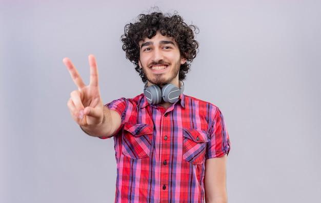 Un hombre guapo feliz con el pelo rizado en camisa a cuadros mostrando dos dedos
