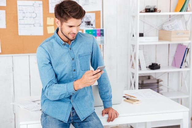 Hombre guapo feliz sentado en la oficina y escribiendo un mensaje en el teléfono móvil