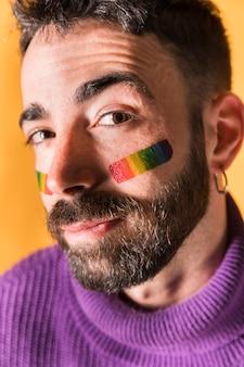 Hombre guapo feliz con el símbolo lgbt en la cara