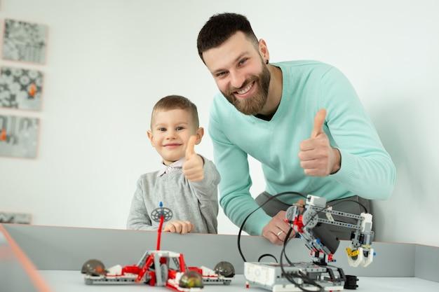 Hombre guapo feliz sonríe a la cámara con su pequeño hijo alegre mientras juega con robots lego