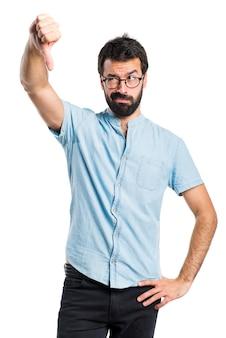 Hombre guapo con gafas azules haciendo mala señal